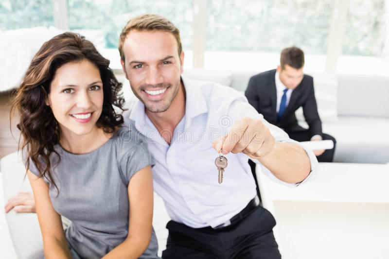 Happy young couple holding new house key royalty free stock photography