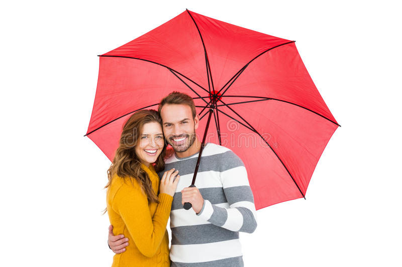 Happy young couple holding pink umbrella. Portrait of happy young couple holding pink umbrella together on white background stock images