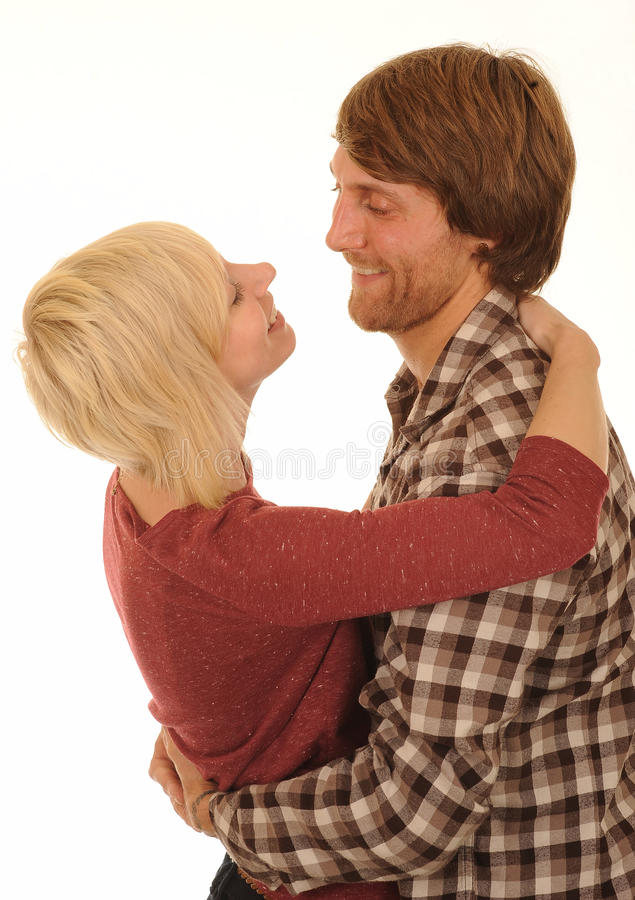Happy young couple hugging. Side view of happy young couple in casual clothes hugging or embracing, isolated on white background stock photo