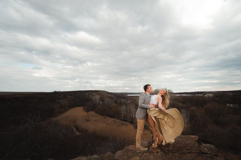 Happy young couple hugging on the edge of the mountain, in the background a very beautiful landscape. stock image