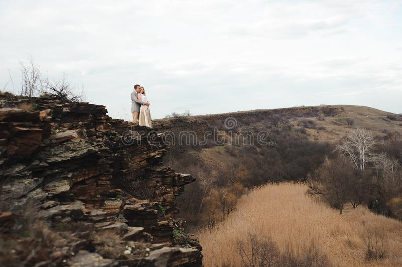 Happy young couple hugging on the edge of the mountain, in the background a very beautiful landscape. royalty free stock image