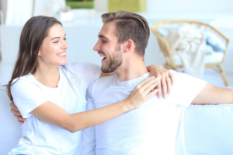 Happy young couple hugging and looking at each other at home interior. royalty free stock photography