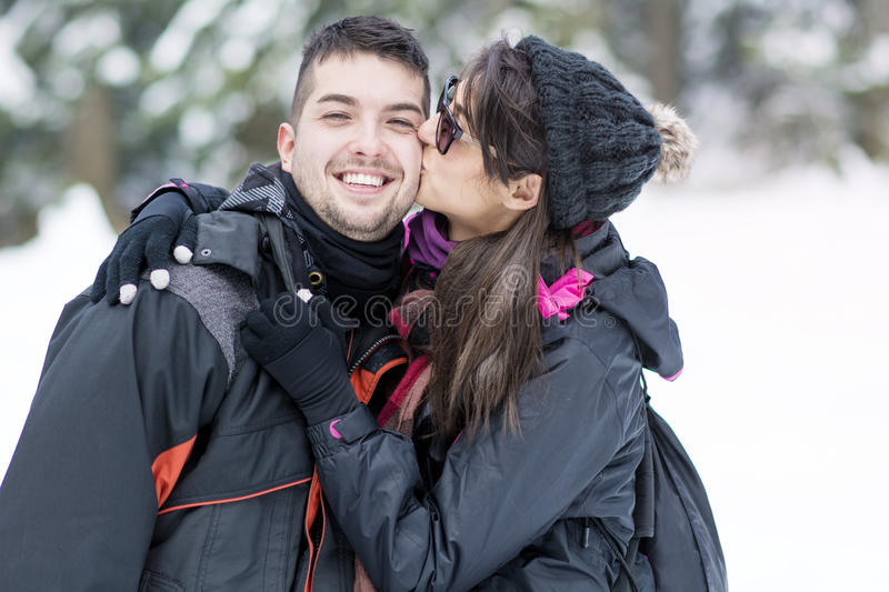 Happy young couple kissing in the winter mountain. Portrait of a Beautiful couple hugging and kissing outdoor in the winter mountain .Bulgaria ,Borovets.Ski stock photo