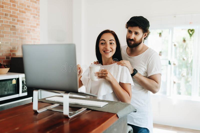 Happy young couple with laptop at home royalty free stock image