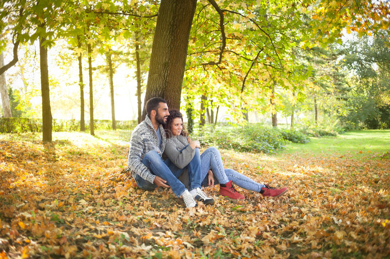 Happy young couple leaning against a tree enjoying the autumn in stock images