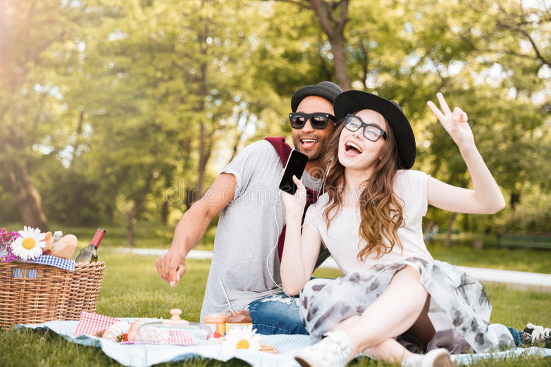 Happy young couple listening to music from smartphone in park royalty free stock photo
