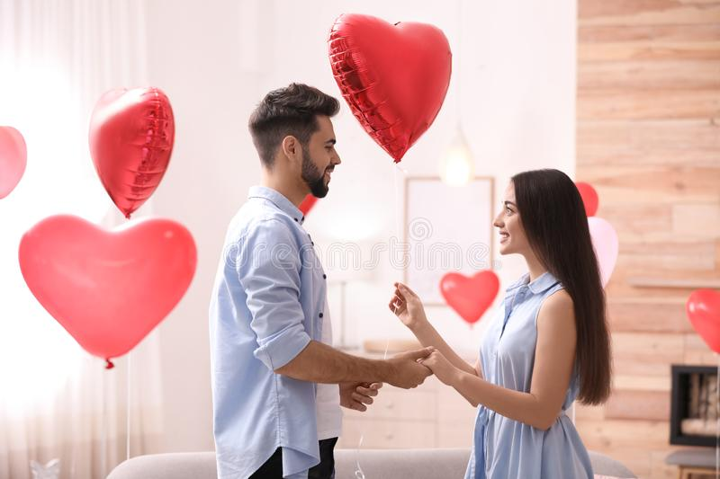 Happy young couple in room decorated with heart shaped balloons. Valentine`s day celebration. Happy young couple in living room decorated with heart shaped royalty free stock images