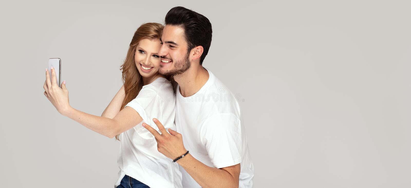 Happy couple taking selfie by mobile phone. Happy young couple looking at camera of mobile phone, making selfie portrait, wearing white t shirts and jeans royalty free stock photography