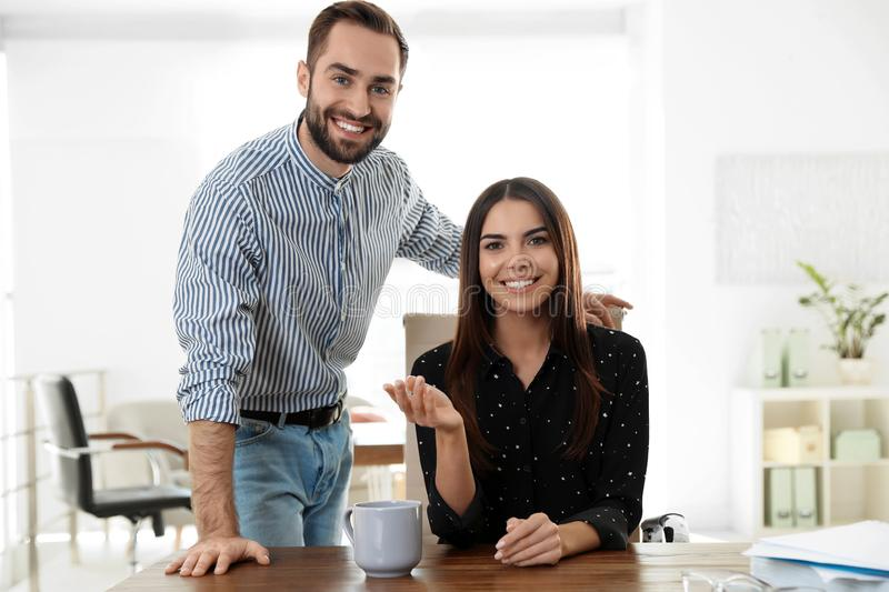 Happy young couple looking at camera and using video chat i. N home office stock images