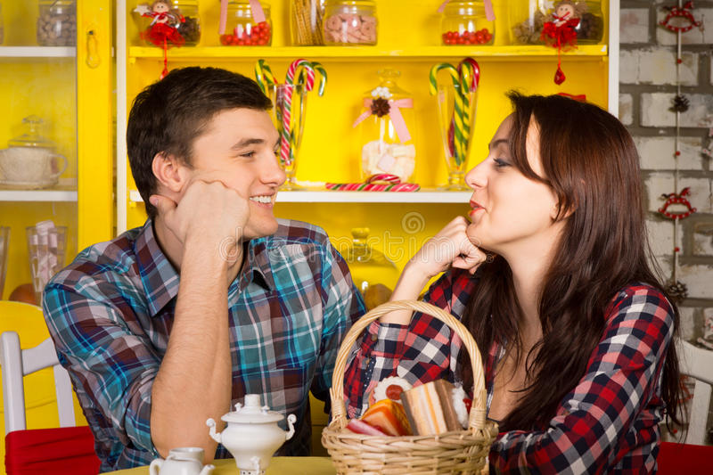 Happy Young Couple Looking Each Other at the Cafe. Close up Happy Young White Couple in Casual Outfits Looking Each Other with Hands on their Face While Having a royalty free stock image