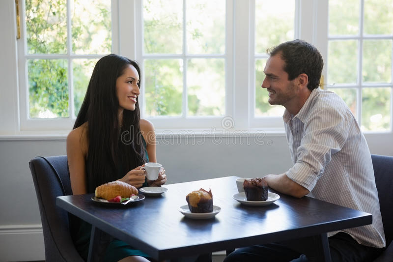 Happy young couple looking at each other while sitting at cafe stock photos