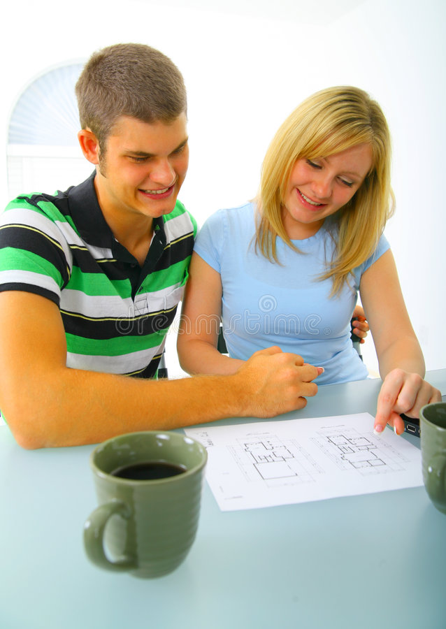 Happy Young Couple Looking At House Floor Plan. Happy young caucasian couple looking at real estate floor plan before purchasing a house royalty free stock photos