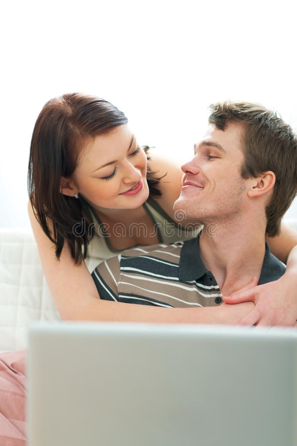 Happy young couple looking in laptop