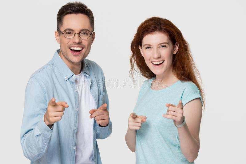Happy couple looking pointing fingers at camera isolated on background stock images