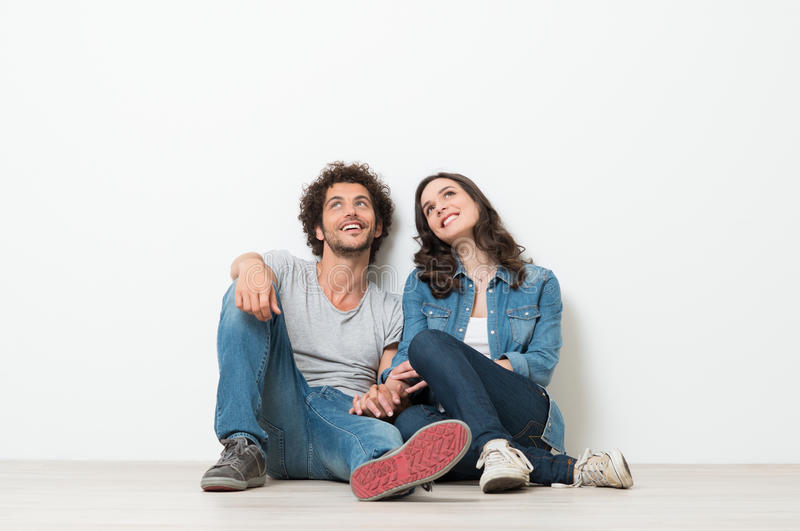 Happy Young Couple Looking Up. Portrait Of Happy Young Couple Sitting On Floor Looking Up Ready for your text or product