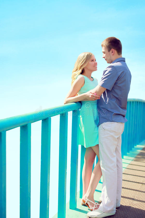 Happy young couple in love on the bridge over blue sky at city park - valentines day relationships concept royalty free stock images