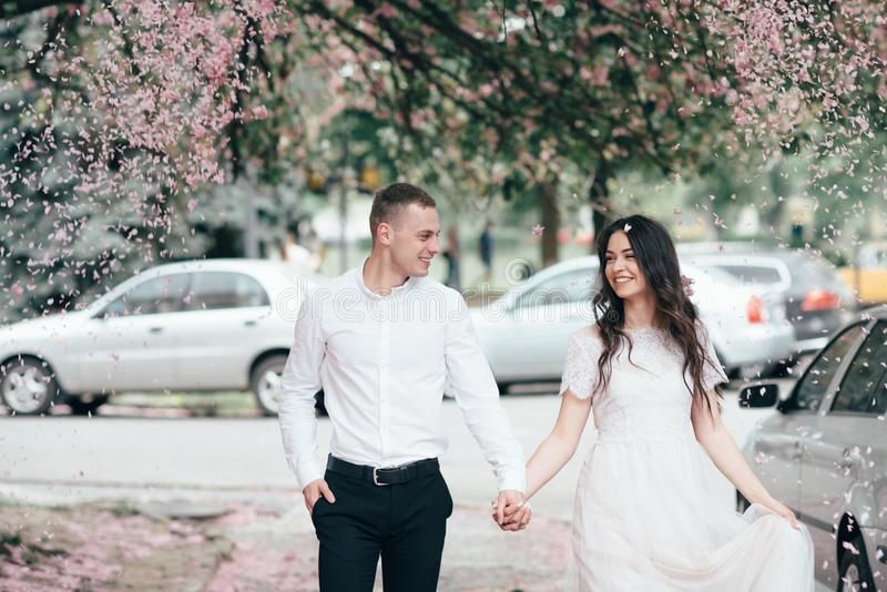 Happy young couple in love enjoys spring day, loving man holding on hands his woman carefree walking at park royalty free stock photography