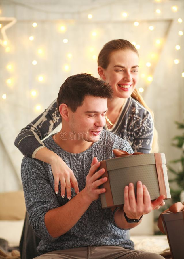 Happy young couple in love give gifts present holiday at home. Happy young couple in love give gifts present in holiday at home stock image