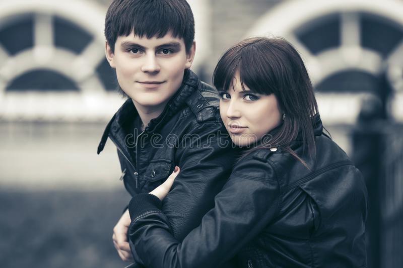 Happy young couple in love hugging in city street. Happy young men and women in love wearing black leather jackets hugging in city street stock photo