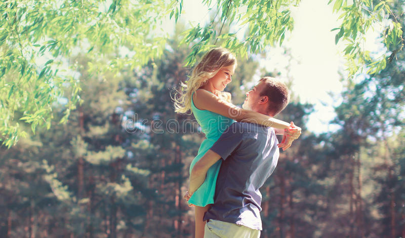 Happy young couple in love hugging enjoys spring day, loving man holding on hands his woman carefree together outdoors walking royalty free stock photography