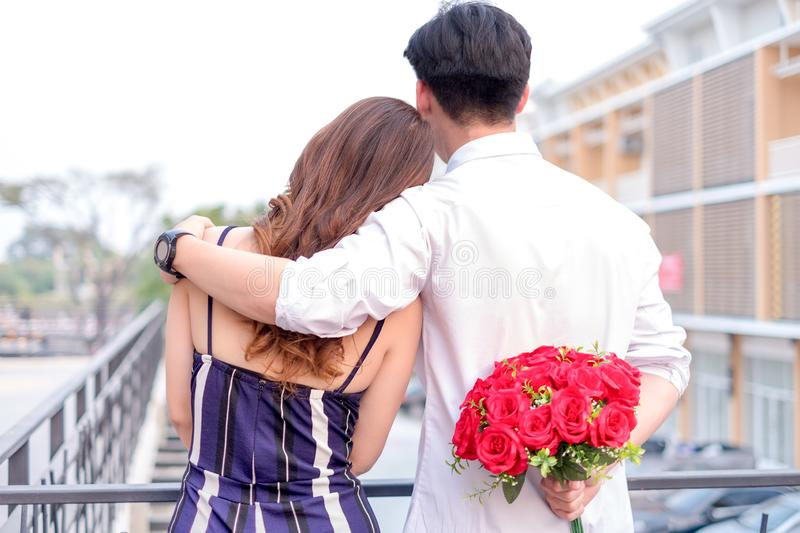 Happy young couple in love hugging and holding red roses in the hands for surprise his girlfriend, couple concept, valentine`s da royalty free stock images