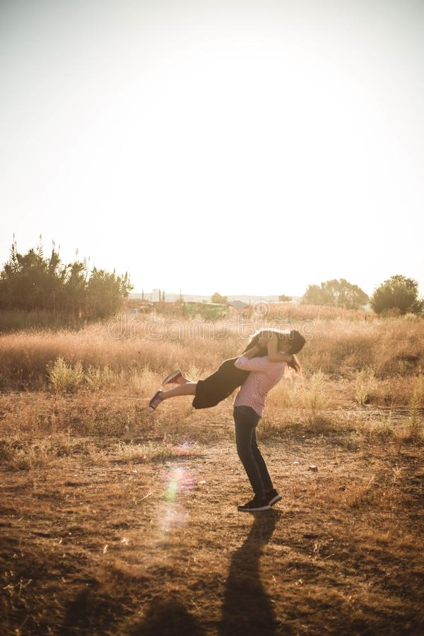 Happy young couple in love, hugging, she is jumping,he is holding her in embrace, enjoying outdoors in a wheat field at sunset stock photo