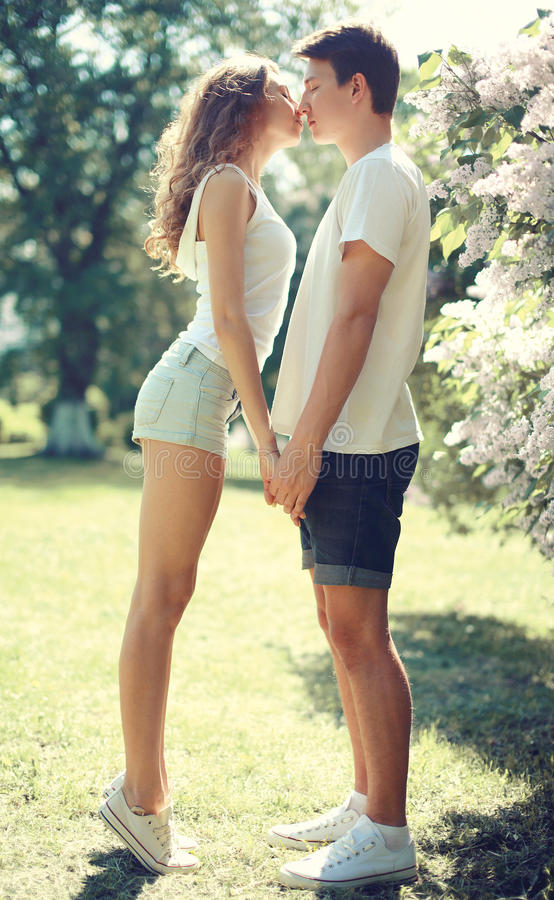 Happy young couple in love, sensual kiss at sunny warm spring royalty free stock photo