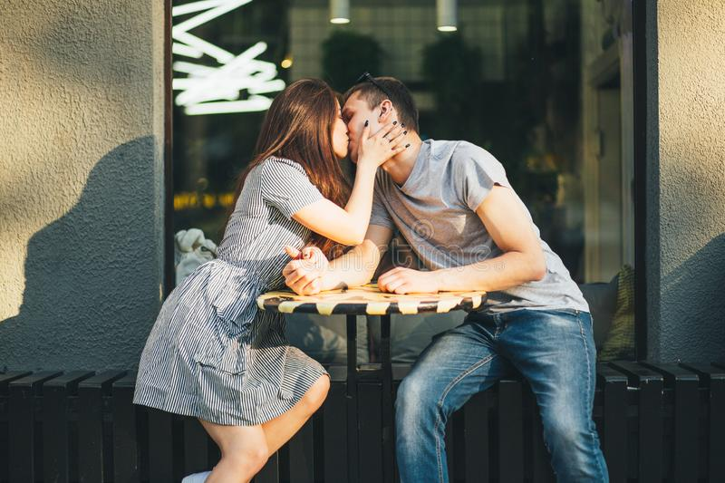 Happy young couple in love teenagers friends dressed in casual style kissing in street cafe stock image