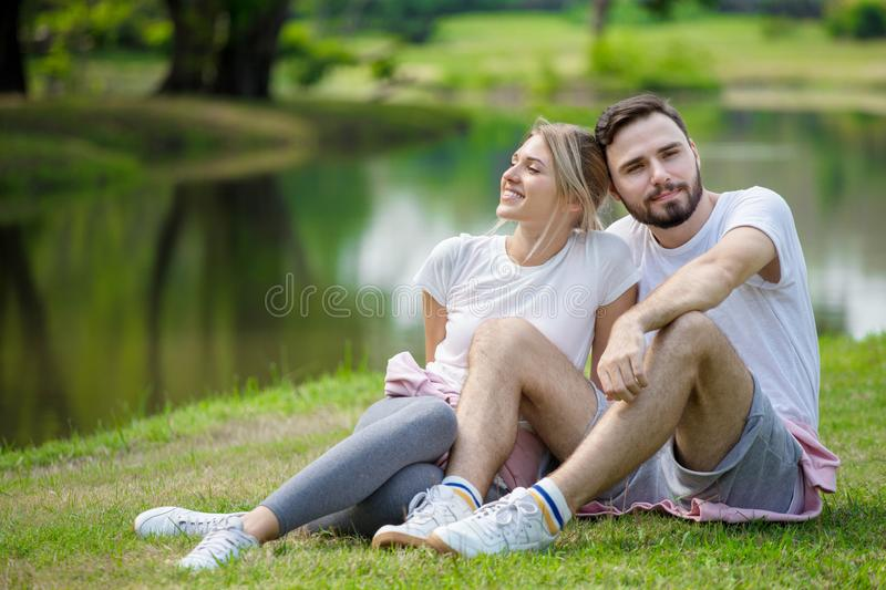 Happy young couple loving fitness in sportswear relaxing at park together in morning time. sport people sitting taking a break royalty free stock photos