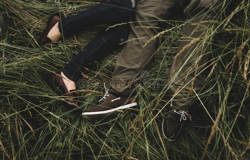 Romantic couple of young people lying on grass in park. royalty free stock photos