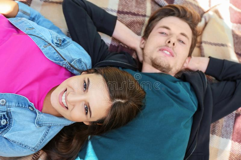 Happy young couple lying on plaid outdoors stock photo