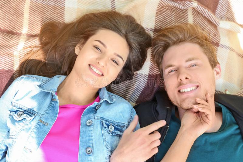 Happy young couple lying on plaid outdoors stock images