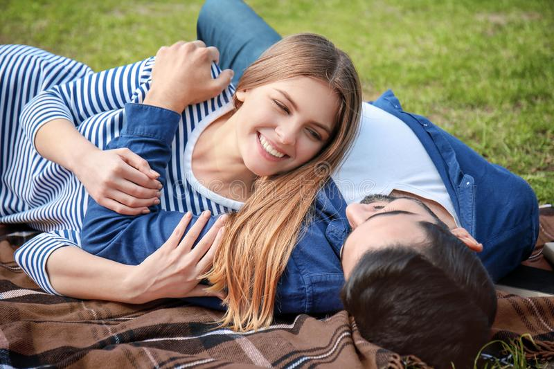 Happy young couple lying on plaid in park stock photos