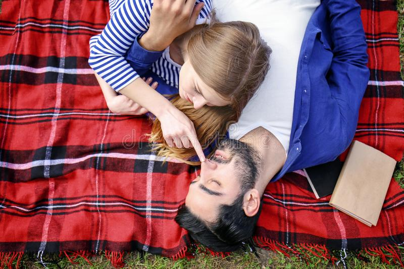 Happy young couple lying on plaid in park royalty free stock images