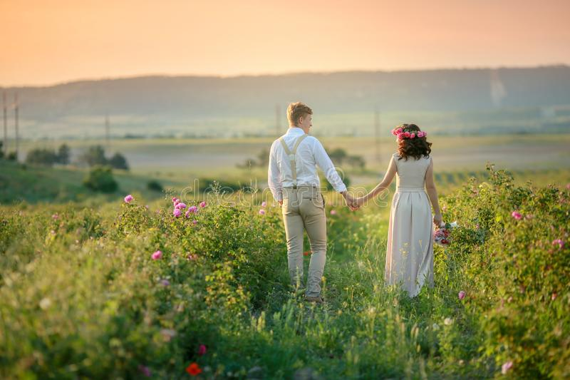 Happy young couple man and woman, adult romantic family. Meet the sunset in a wheat field. Happy smiling. The girl in royalty free stock images