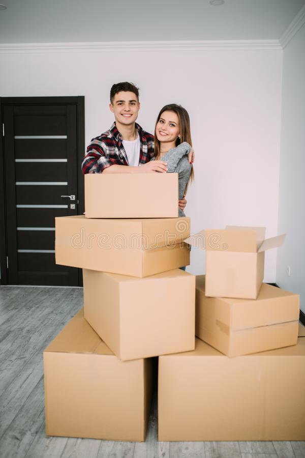 Happy young couple moved to new place to start live together, they are embracing, around many carton boxes with their things. The room is very light and bright royalty free stock images