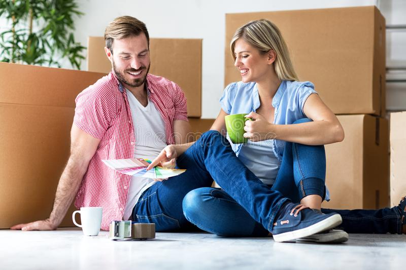 Happy young couple moving in new home unpacking boxes and choosing color royalty free stock images