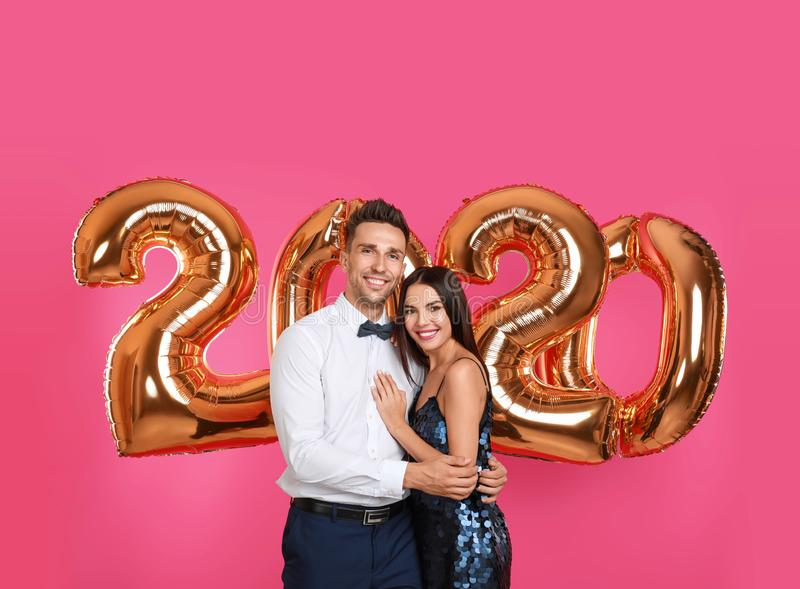 Happy young couple near golden 2020 balloons on pink background stock photography