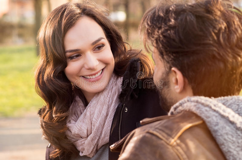 Happy young couple at park. Portrait of happy couple looking at each other and smiling outdoor royalty free stock photos