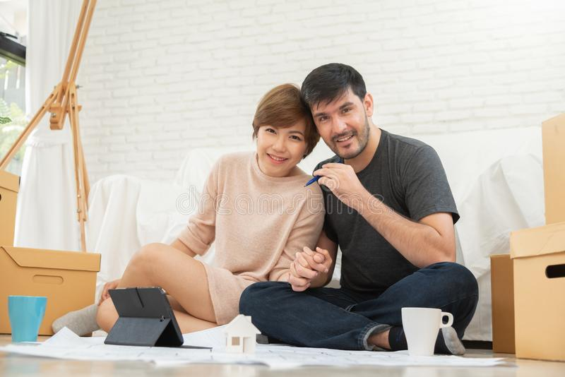 Happy young couple planning their new moving house. stock photo