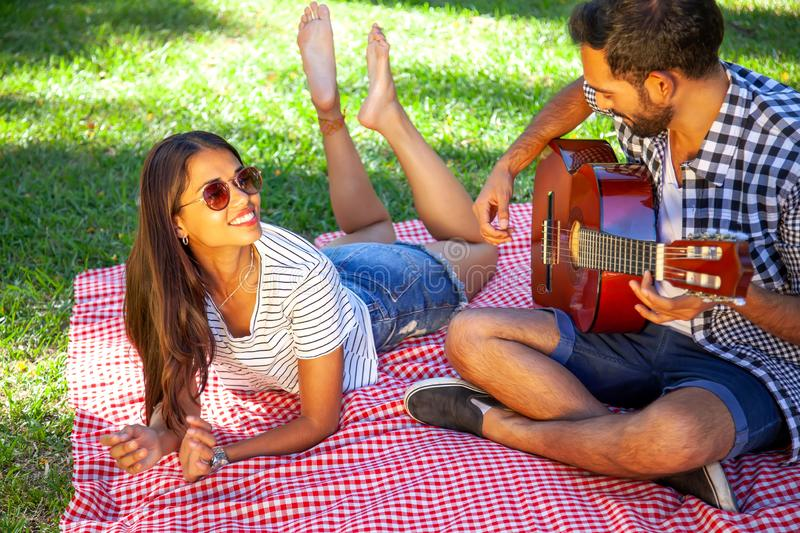 Happy couple playing guitar outdoors royalty free stock photo