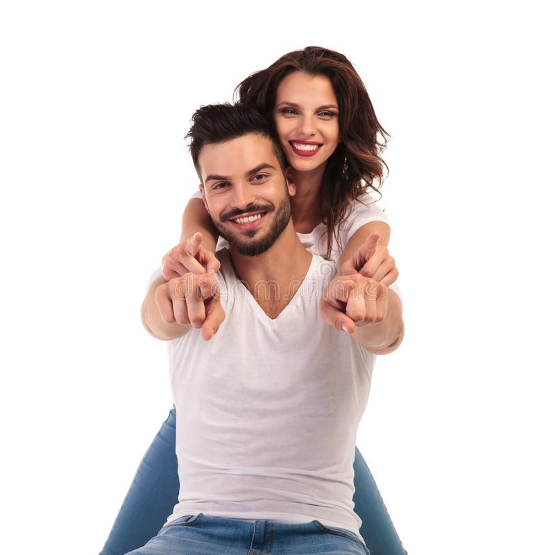 Happy young couple pointing fingers together stock photo
