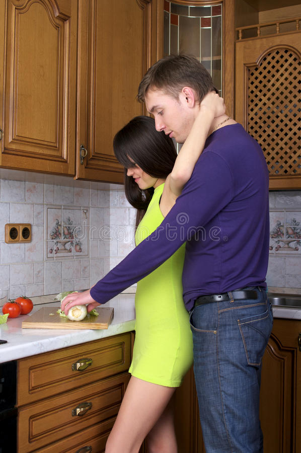Happy young couple preparing food stock photography