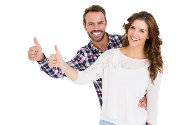 Happy young couple putting thumbs up royalty free stock photography