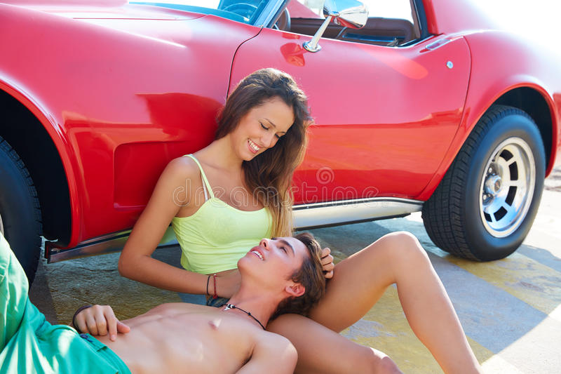Happy young couple relaxed in a car side sitting stock image