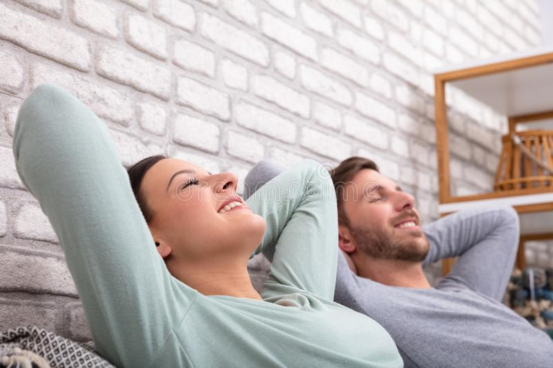 Couple Relaxing On Sofa. Happy Young Couple Relaxing On Sofa At Home royalty free stock photos