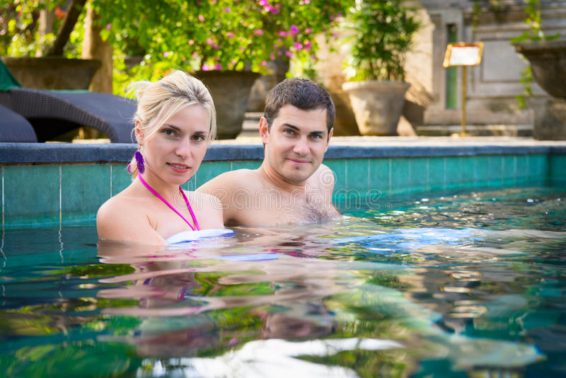Happy young couple relaxing in a swimming pool stock photography