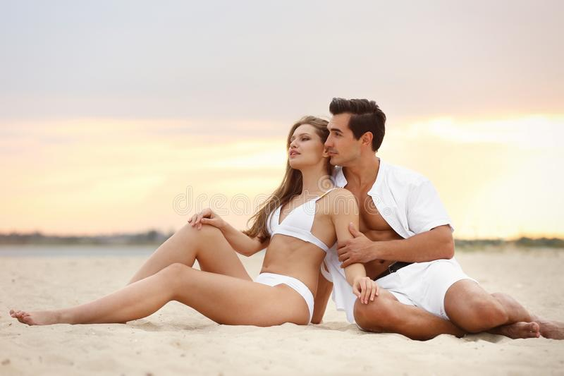 Happy young couple relaxing together on sea beach at royalty free stock images
