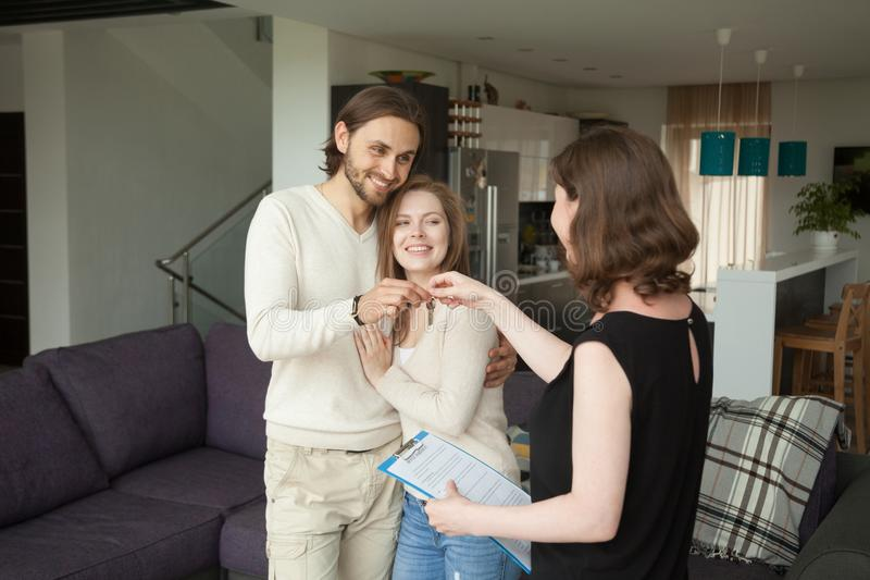 Happy young couple renters getting keys of new rental home royalty free stock images