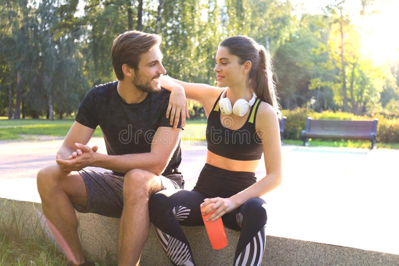 Happy young couple resting together with bottle of water outdoors after jogging royalty free stock photography